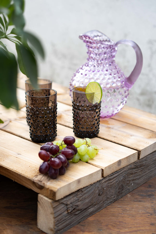 Black Smoke Hobnail Tumblers on a wooden block with green and purple grapes and lilac hobnail jug behind the tumblers