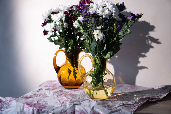 Citrine and Amber Marika Jugs with flowers inside standing on a table
