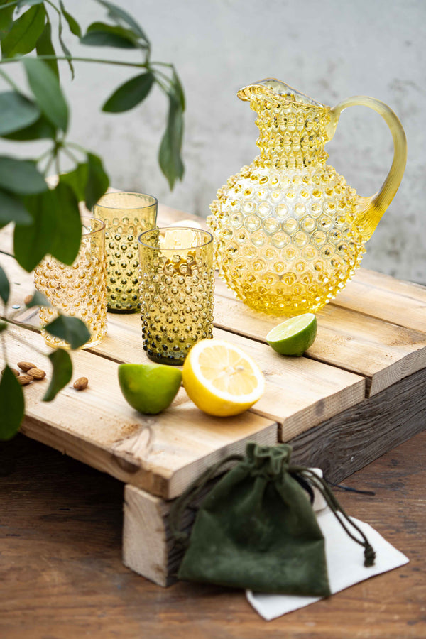 Citrine Hobnail Jug with two Bonsai Green Hobnail Tumblers and one Underlay Amber Hobnail Tumbler with lemons and limes on a wooden box