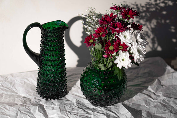 Dark Green Hobnail Round Vase with flowers alongside matching Hobnail Jug Tall