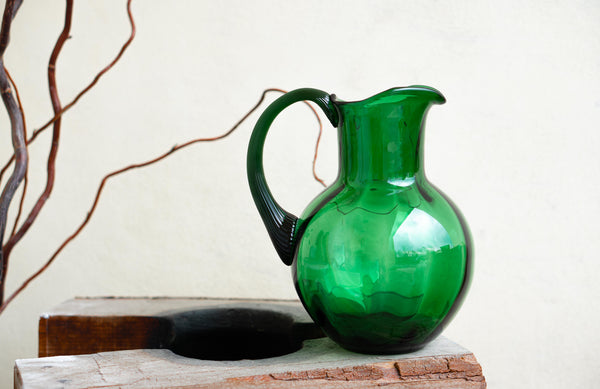 Dark Green Marika Jug on a piece of wood. There's a light cream wall behind it