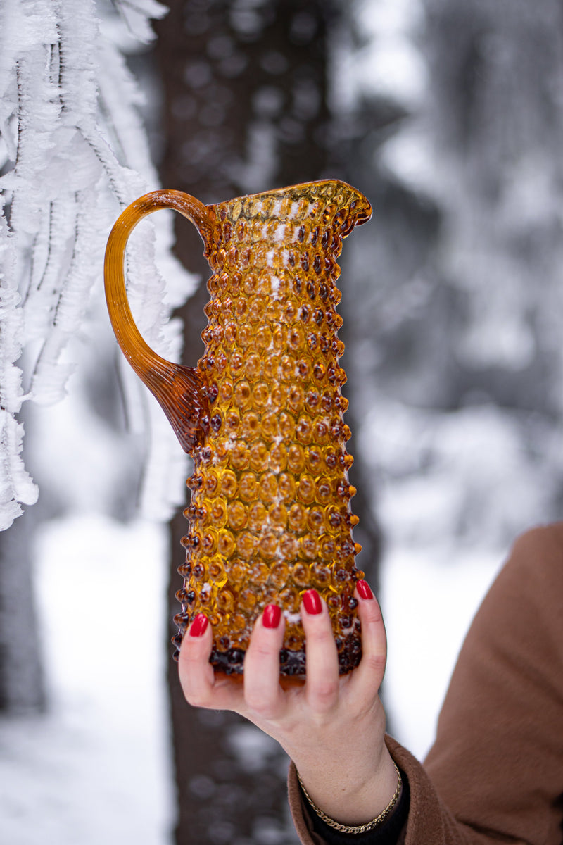 Hand of a Lady Holding Slim Glass Amber Pitcher