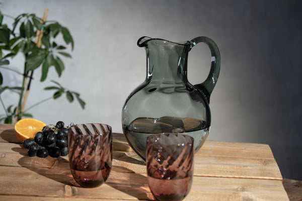 Grey Smoke marika jug with a pair of violet marika tumblers on a wooden table with purple grapes and a half of orange