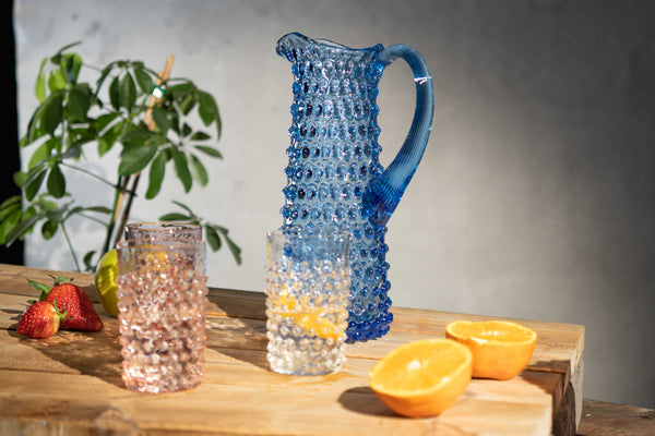 Light Blue Hobnail pitcher with a set of hobnail tumblers on a wooden table surrounded by fruits