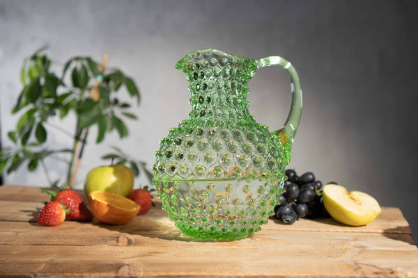 Hobnail pitcher in light green on a wooden table with different fruits behind it.
