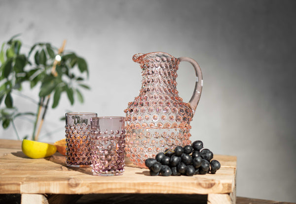 Rosaline Hobnail Square jug with two underlay violet hobnail tumblers on a wooden table with fruits and a plant behind the glassware