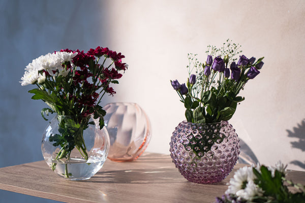 Violet Glass Vase and Crystal Vase with Flowers on the table and pink round vase in behind