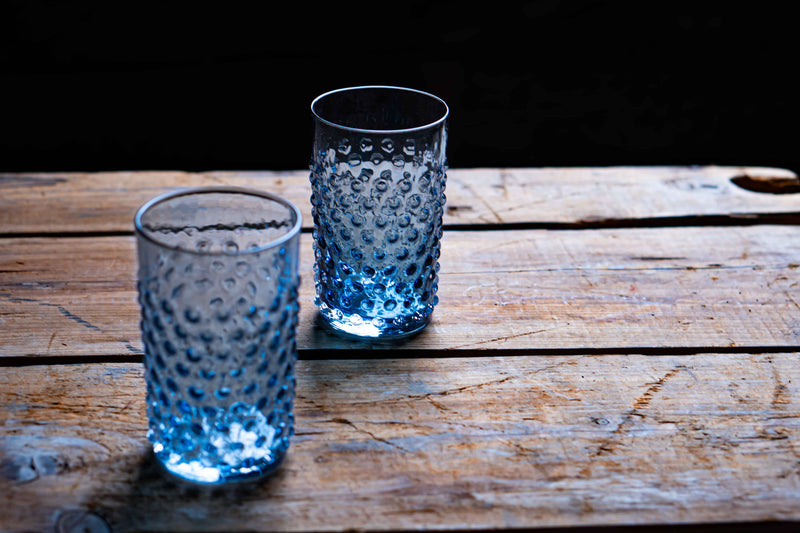 Two Underlay Blue Smoke Hobnail Tumblers on a wood table