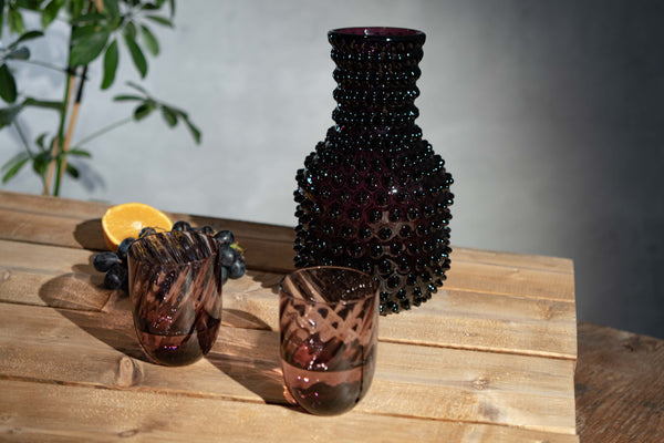 Violet Hobnail Carafe with two violet tumblers in marika on a rustic table