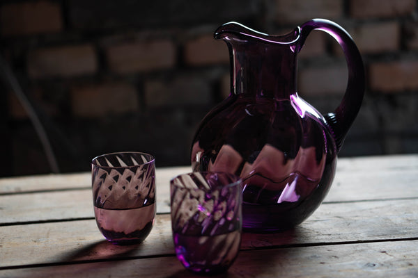 Violet glass jug on a wooden bench with two matching tumblers.