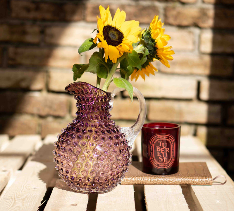 Underlay Violet Glass Jug with Sunflowers in it and Candle besides