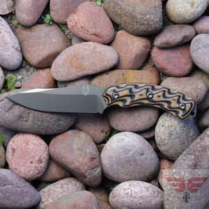 Southern Grind Jackal is a fixed blade knife with a black and tan 3D milled handle and full tang blade made from 8670M high carbon steel with a pvd coating.  Made in the USA - Shown with a stone background