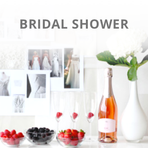 Bridal shower table setting with flowers and fruit and bridal gown pictures hanging