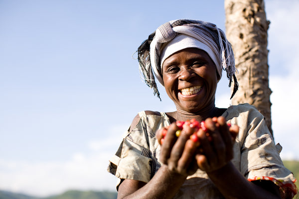 Women holding freshly picked coffee beans with blue sky