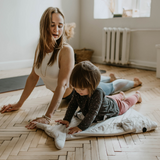 Mother and child practising yoga on the floor
