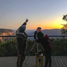 Load image into Gallery viewer, Man pointing towards to the sky with a girl looking through a telescope next to him. Both experiencing the stars, enjoying sunset over the Blue Mountains.