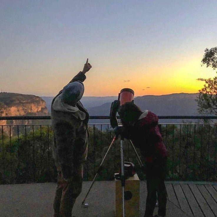 Man pointing towards to the sky with a girl looking through a telescope next to him. Both experiencing the stars, enjoying sunset over the Blue Mountains.