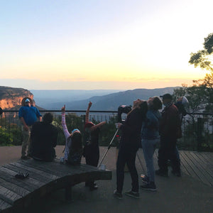 4 adults standing, looking up, 2 kids sitting, looking up and pointing towards the sky, 1 adult sitting looking at the stars and their host standing and looking up. All outside experiencing star gazing in the Blue Mountains.