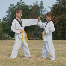 Load image into Gallery viewer, Two children in their white uniform with yellow belts learning martial arts