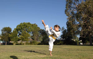Girl in white uniform with yellow belt high kicking in marital arts class outside