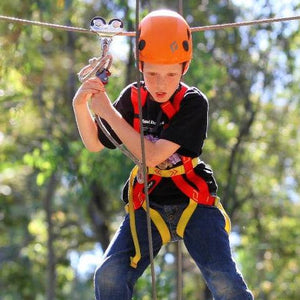 Boy with orange helmet experiencing high ropes course