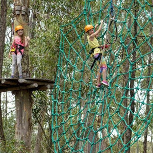 Two girls experiencing the rope spiderweb, one climbing, one watching