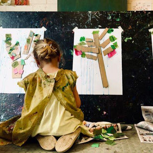 A young child facing their painting with a smock on in art classes for kids