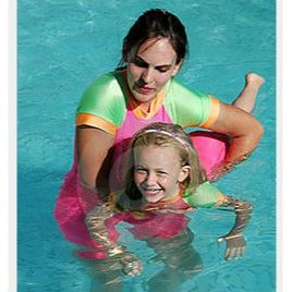 Teacher in green, pink & orange swim shirt holding, floating on stomach a blonde girl in the pool during swimming lessons.