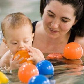 Mother with dark hair pulled up looking & holding her baby in the pool surrounded by floating blue, orange balls during swim class.