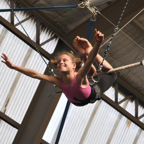 Happy girl experiencing flying on a trapeze mid-air.