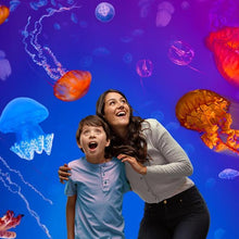 Load image into Gallery viewer, Mother with dark long hair, grey shirt hugging her son with dark short hair, blue shirt. Both have their mouth open in awe of experiencing colourful jellyfish swim around them at Melbourne aquarium.