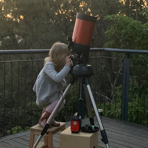 Young blonde girl looking through a large telescope up at the stars outside. Experiencing star gazing in the Blue Mountians