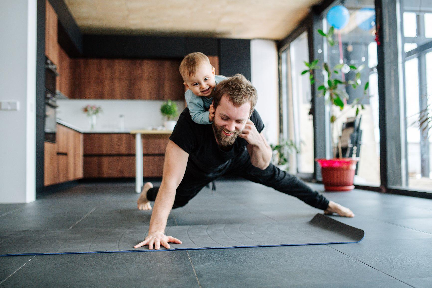 Man doing one arm push up with small child on his back