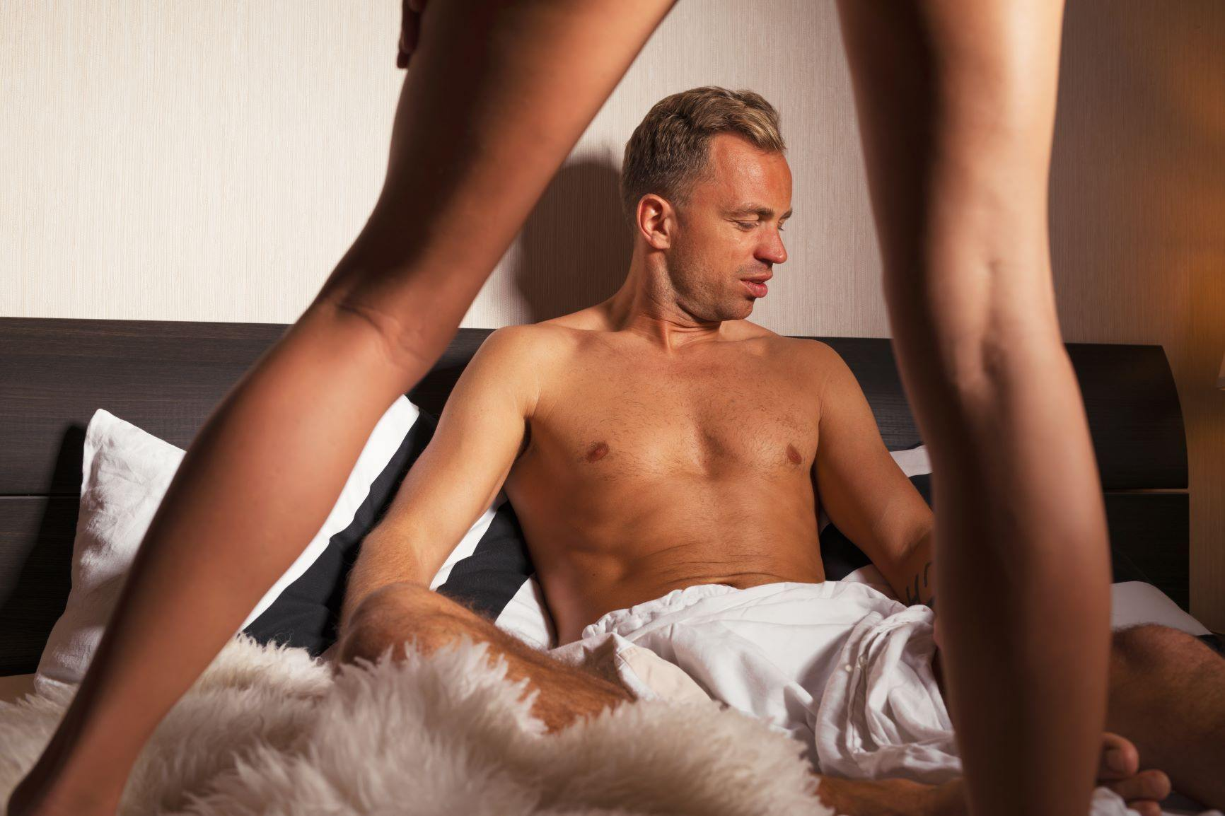 Man sitting in bed without shirt and woman's bare legs in forefront
