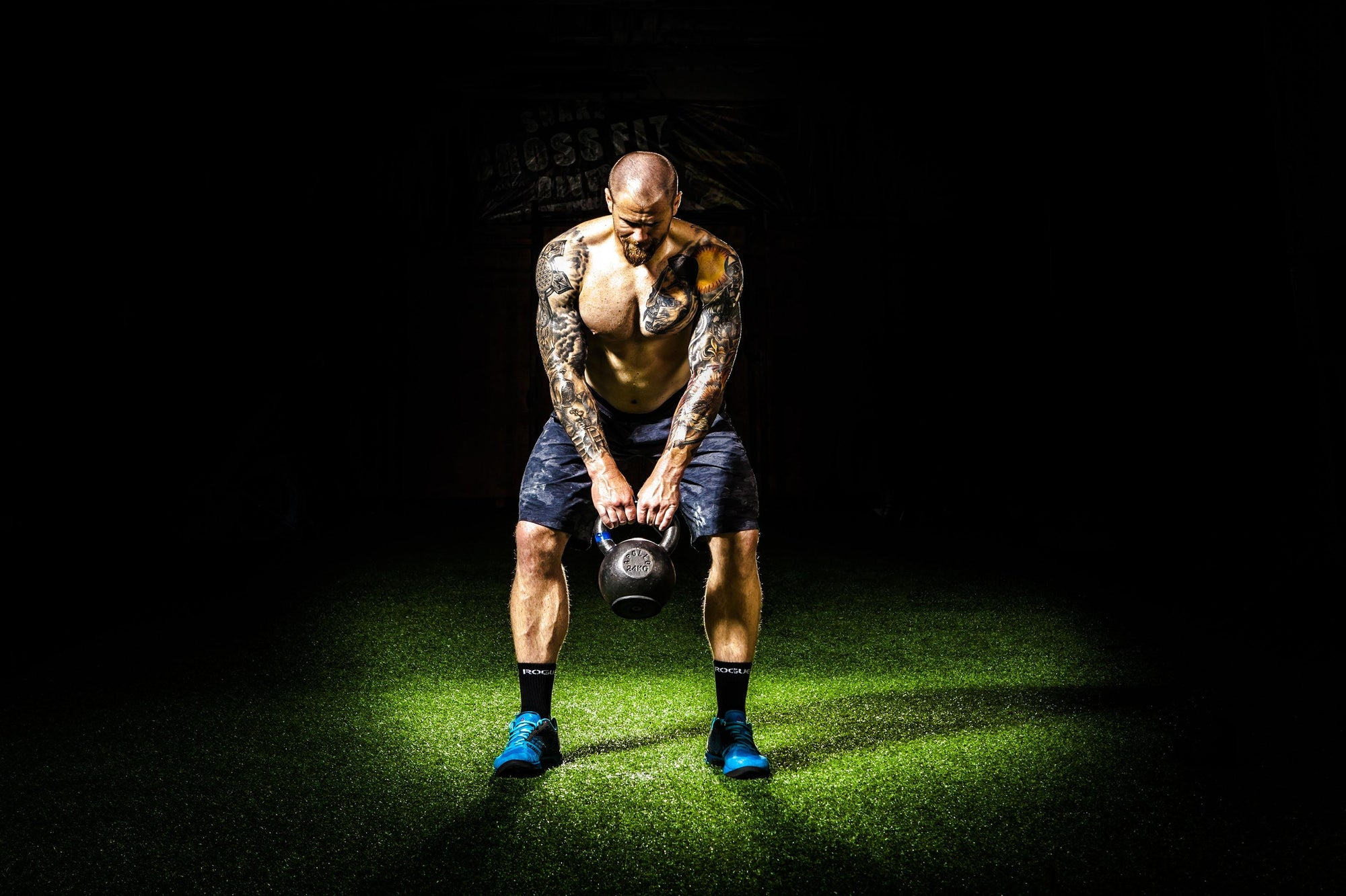 Physically fit man with tattoos working out with a kettle bell
