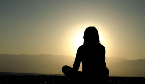 woman sitting cross legged looking at a sunset over a mountain range
