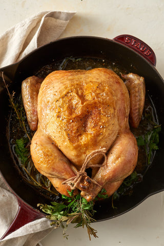 whole roasted chicken in cast iron pan with herbs