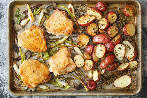 baking sheet with baked chicken roasted potatoes and veggies