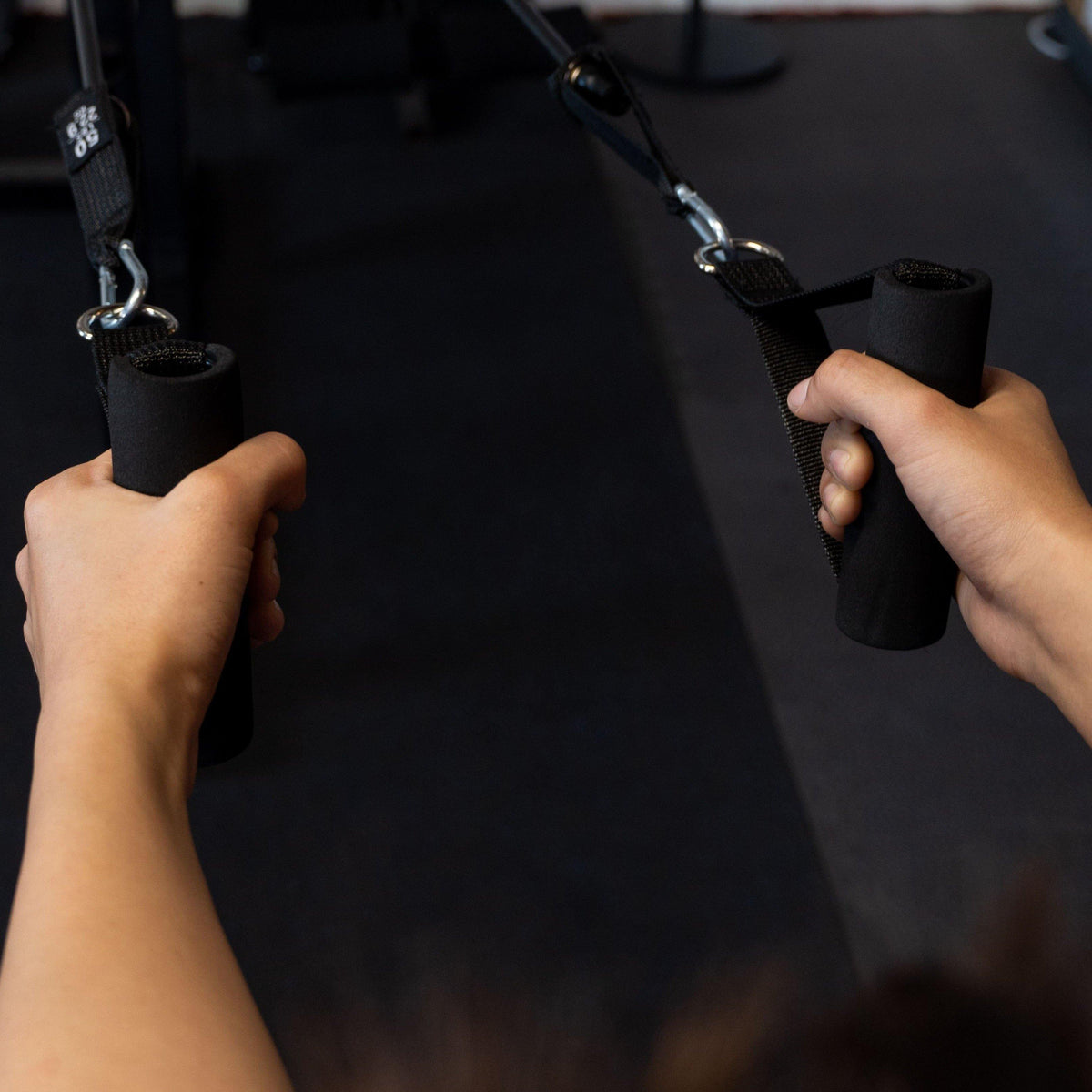 Trainer working out arms and chest using Spartan Resistance bands at the gym.