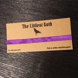 Front on version The Littlest Goth DL backing card printed on kraft card with black crow design and social media information with purple ribbon tied round