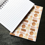 Inside lined pages of A5 notebook with full page example of various different types of biscuits printed across the page