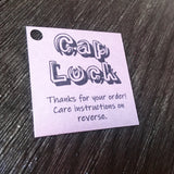 Cap Lock single example close up thank you for your order care instructions small square black and white swing tag with 5mm round hole