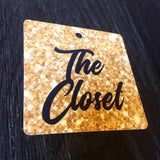 Close  up of black and gold sparkle effect square The Closet swing tag with 5mm round hole