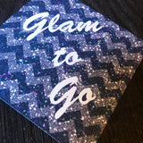 Close up of blue and purple zig zag effect with white Glam to Go wording square swing tag with 5mm round hole