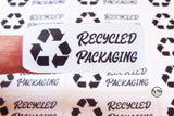 Close up of black and white rectangular recycled packaging click and go sticker with recycled icon made from recycled paper