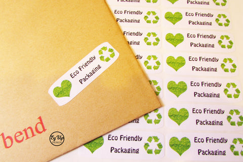 Eco friendly white and black rectangular stickers with green heart and recycling icon attached to an envelope with sheet of stickers behind