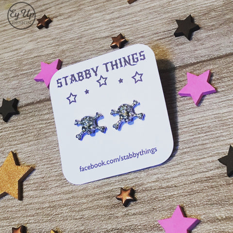 White and purple Stabby Things earring backer card with skull earrings and facebook link printed on brilliant white card