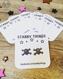Fan layout of Stabby Things purple and white earring backer cards with skull earrings and Facebook link printed on brilliant white card