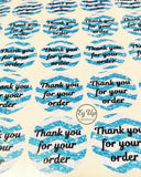 Sheet of blue chevron thank you for your order round stickers on white background with black writing