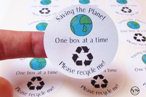 Close up of Saving the Planet one box at a time black and white 45mm round stickers with earth icon and please recycle me wording and icon